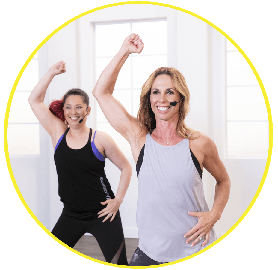 Shanna Nelson and Young McCarthy of Jazzercise dancing with right arm up in studio