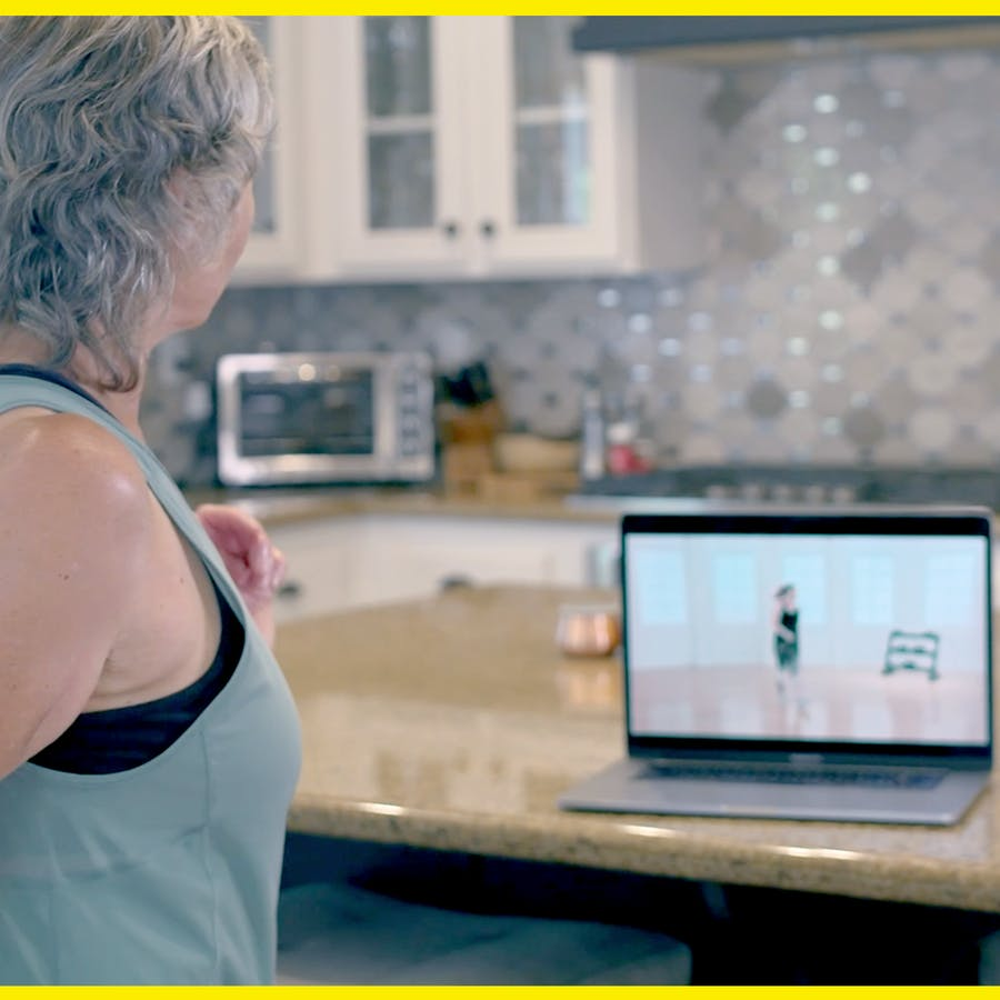 Gray-haired woman exercising to Jazzercise On Demand on her laptop in her kitchen