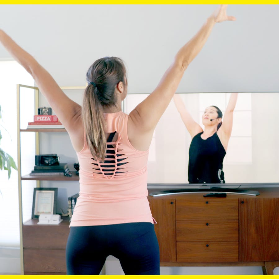 Brown-haired woman with a ponytail exercising to Jazzercise On Demand on her TV in her living room